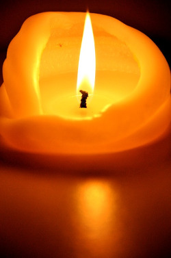 A large lit candle with wax folding inward