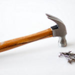 "Image of a hammer with a wooden handled resting face down on a white surface with a small pile of 2"" nails nearby"