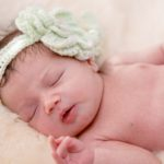 baby girl with mint green crocheted floral band sleeping