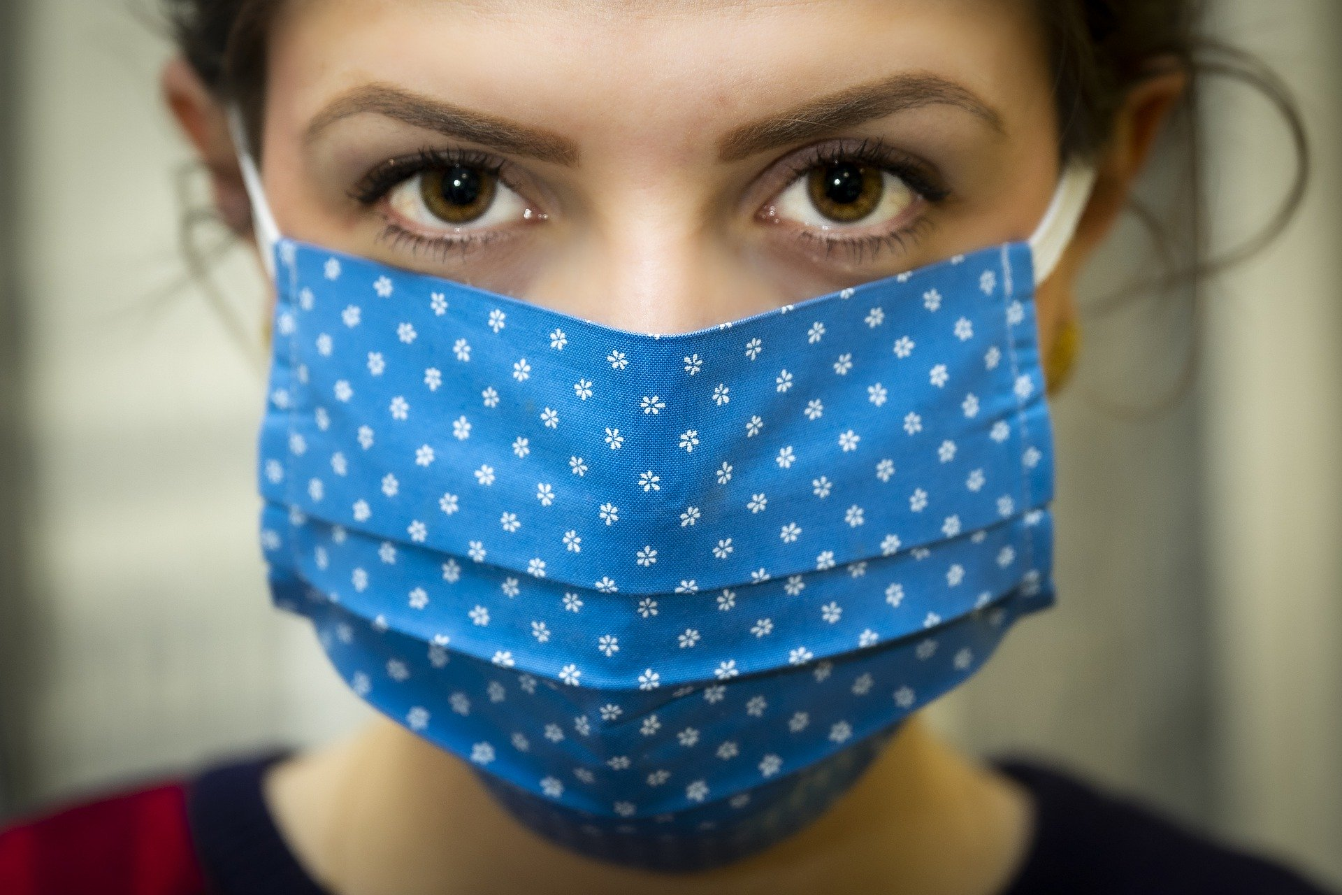 Brown eyed woman facing camera wearing a navy blue with white spotted mask