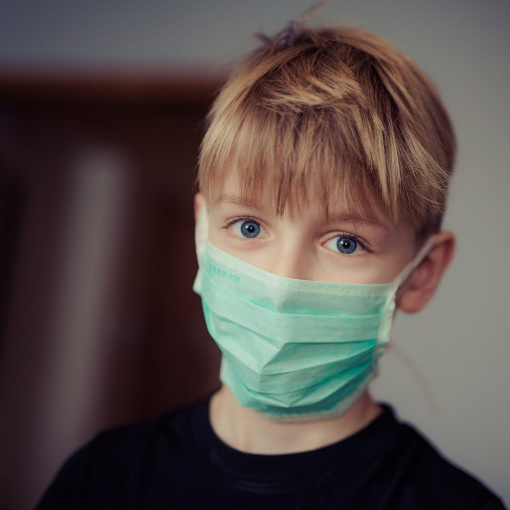 blonde haired white boy wearing a green tinted surgical mask facing camera